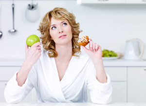 Thinking beautiful woman choosing between healthy food and caloric food - indoors