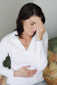 Женщина с болью в голове и в желудке